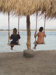 Back view of two women sitting on swings at seafront, Gili Islands, Bali - KNTF03639