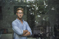 Portrait of casual young businessman behind windowpane in office - PNEF02084