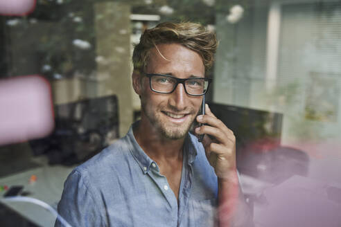 Portrait of smiling young businessman on the phone behind windowpane in office - PNEF02090