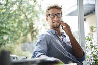Casual young businessman on the phone at desk in office - PNEF02096