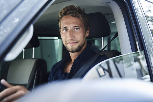 Portrait of confident young man in car - PNEF02099