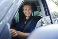Portrait of smiling young man in car - PNEF02102