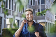 Smiling young businessman on the phone in the city - PNEF02111