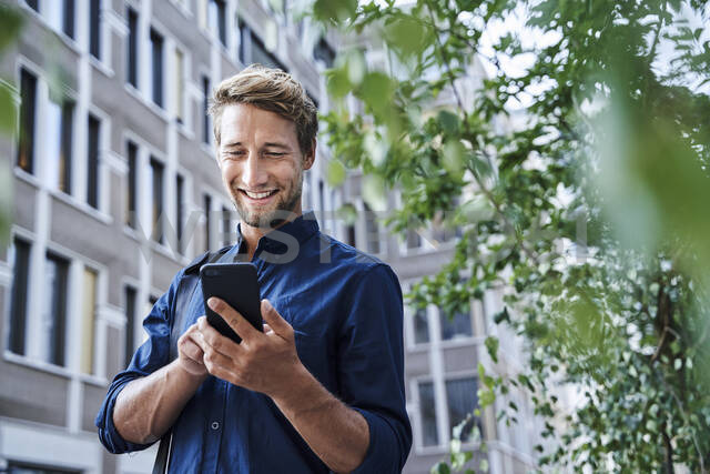 Smiling young businessman using mobile phone in the city - PNEF02114 - Philipp Nemenz/Westend61