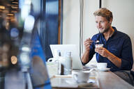 Young businessman eating and using laptop in a cafe - PNEF02138