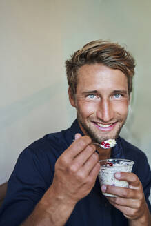 Portrait of smiling young man eating muesli - PNEF02141