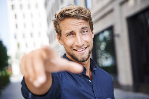 Portrait of confident young man in the city pointing his finger - PNEF02162