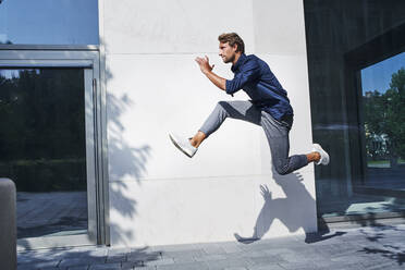Young businessman jumping mid-air in the city - PNEF02165
