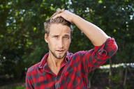 Portrait of young man wearing checkered shirt outdoors - PNEF02168
