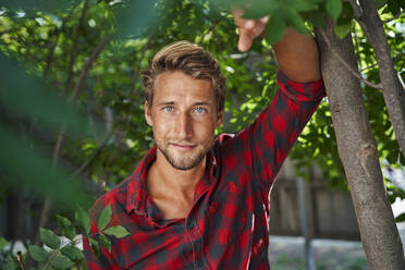 Portrait of confident young man wearing checkered shirt leaning against a tree - PNEF02171