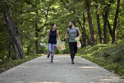 Couple plogging on forest path - ZEDF02615