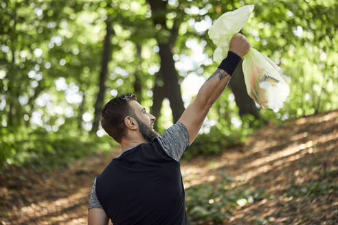Sporty man holding litter bag in forest - ZEDF02624