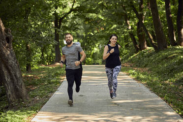 Sporty couple running on forest path - ZEDF02627