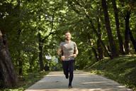 Sporty man running on forest path - ZEDF02630