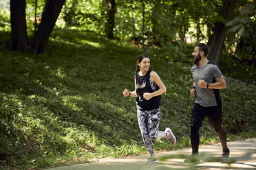 Sporty couple running on forest path - ZEDF02633