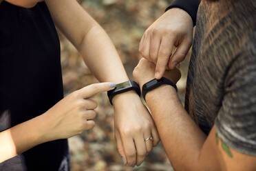 Close-up of sporty couple checking smartwatches - ZEDF02636