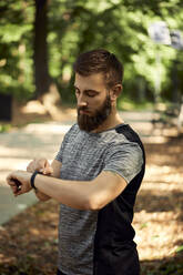 Sporty man in forest checking his smartwatch - ZEDF02639
