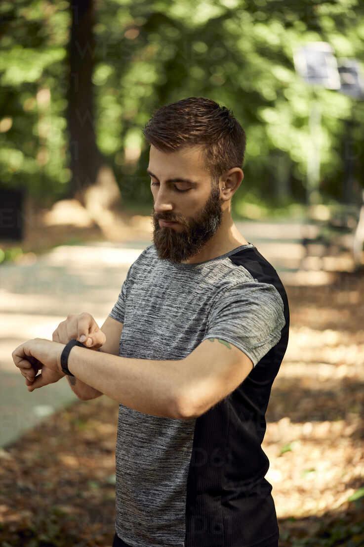 Sporty man in forest checking his smartwatch - ZEDF02639 - Zeljko Dangubic/Westend61