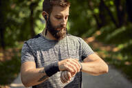 Portrait of sporty man with earphones in forest checking his smartwatch - ZEDF02642
