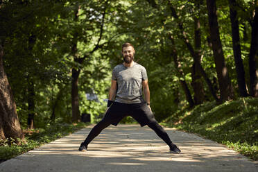 Sporty man stretching on forest path - ZEDF02645