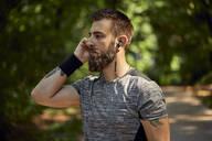 Portrait of sporty man with earphones in forest - ZEDF02648