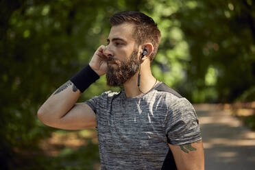 Portrait of sporty man with earphones in forest - ZEDF02648