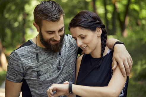 Happy sporty couple checking smartwatch - ZEDF02651
