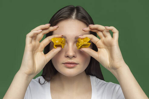 Portrait of young woman covering eyes with tortellini - VGF00302