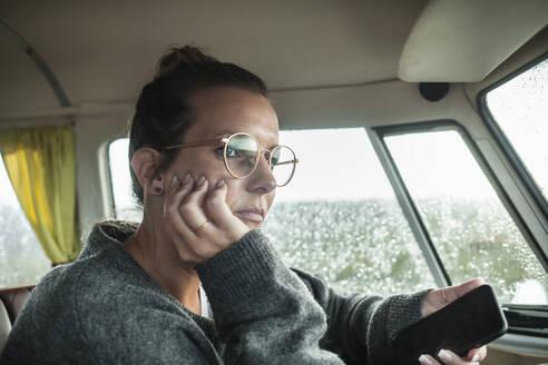 Woman with smartphone in a van looking sideways - NAF00128