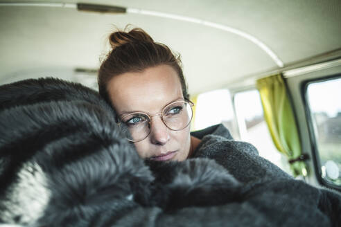 Woman lying on a blanket in a van - NAF00131