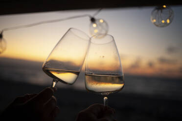 Woman holding two glasses of white wine in van at sunset - NAF00140