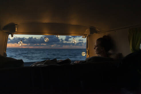 Woman in a van looking sideways at sunset - NAF00146