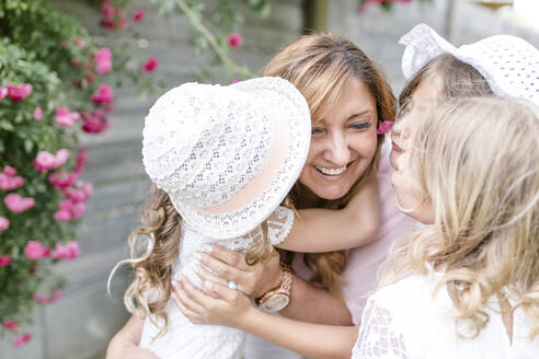 Triplet sisters hugging and kissing happy mother - STBF00430