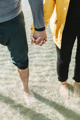 Couple holding hands at the beach - NAF00162
