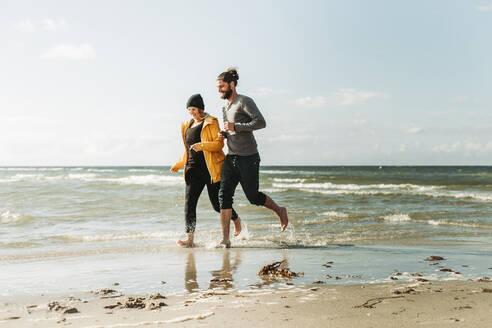 Couple running at the beach in Heiligenhafen - NAF00165