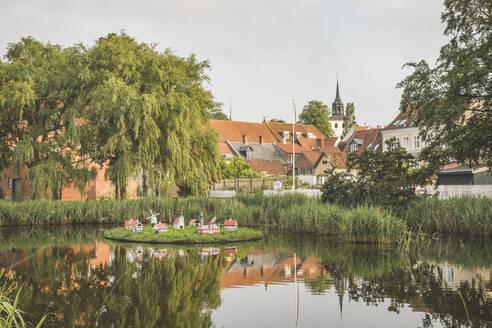 Denmark, Aeroe, Aeroskobing, House figurines on pond seen over water - KEBF01361