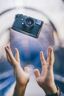 Man hands throwing a vintage camera - CJMF00069
