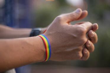 Man hands with gay flag bracelet - CJMF00075