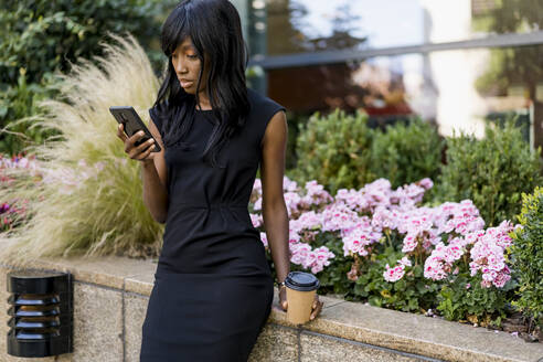 Businesswoman using smartphone in the city - MAUF02916