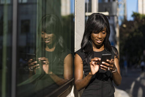 Businesswoman using smartphone in the city - MAUF02931