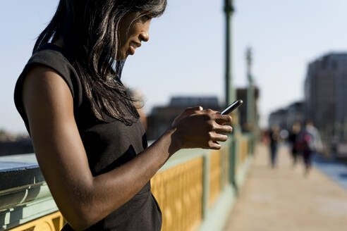 Businesswoman using smartphone on a bridge - MAUF02937