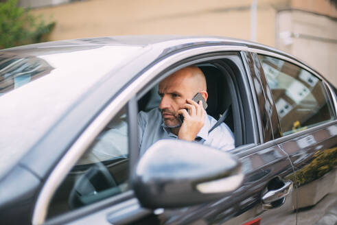 Businessman driving vehicle and using smartphone - CJMF00080