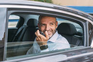 Businessman sitting on a backseat of a car using smartphone and looking around - CJMF00083