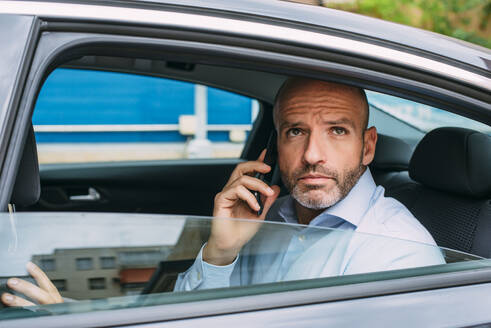 Businessman sitting on a backseat of a car using smartphone and looking around - CJMF00086