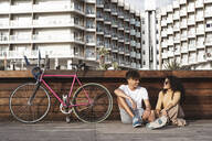 Young couple with bicycle sitting in the city, talking - RCPF00008