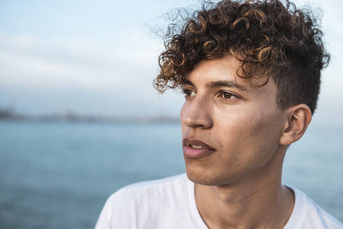 Portrait of young man with curly hair by the sea - RCPF00032
