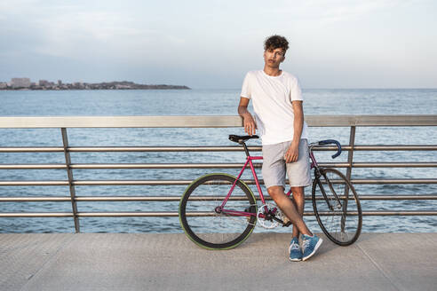 Young man with bicycle,  standing on bridge by the sea - RCPF00035