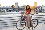 Beautiful wiman in the city with her bicycle - RCPF00050