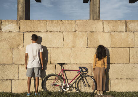 Young couple with bicycle, standing in front of wall, rear view - RCPF00053