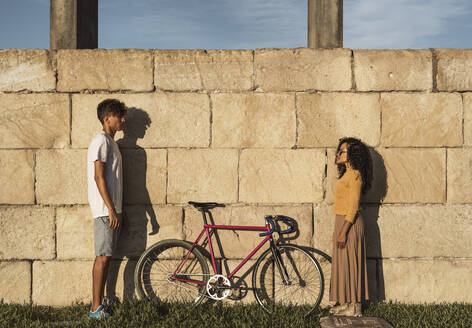 Young couple with bicycle, standing in front of wall, face to face - RCPF00056